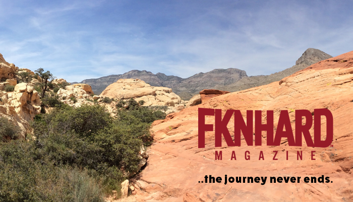 fknhard-magazine-red-rock-desert-mojave-desert-las-vegas-nevada-hiking-mountain-sitting-resting-climbing-trail-runner-hike-valentina-zuniga-red-tanktop-shirt-cliff-bushes-blue-sky-journey-mountains