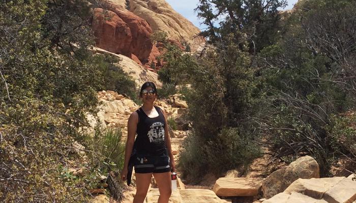 fknhard-magazine-red-rock-las-vegas-nevada-hiking-mountain-climbing-trail-runner-hike-isamar-larrieta-black-tanktop-shirt-pride-rock-cliff-bushes-skull-feather-track-trail